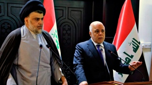 """In this photo provided by the Iraqi government, Iraqi Prime Minister Haider al-Abadi, right, and Shiite cleric Muqtada al-Sadr hold a press conference in the heavily fortified Green Zone in Baghdad, Iraq, early Sunday, May 20, 2018. Shiite cleric Muqtada al-Sadr, whose coalition won the largest number of seats in Iraq's parliamentary elections, says the next government will be """"inclusive."""" The May 12 vote did not produce a single bloc with a majority, raising the prospect of weeks or even months of negotiations to agree on a government. (Iraqi Government via AP)"""