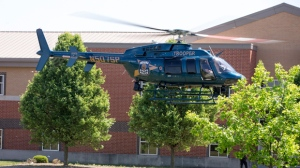 An Indiana State Police helicopter lifts off after a shooting at Noblesville West Middle School in Noblesville, Ind., on Friday, May 25, 2018. A male student opened fire at the suburban Indianapolis school wounding another student and a teacher before being taken into custody, authorities said. (Robert Scheer/The Indianapolis Star via AP)