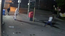 A screenshot of surveillance camera footage shows gunmen chasing a man in Regent Park. (Toronto police)