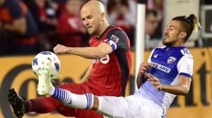 Toronto FC midfielder Michael Bradley (4) and FC Dallas forward Maximiliano Urruti battle for the ball during second half MLS soccer action in Toronto on Friday, May 25,18. THE CANADIAN PRESS/Frank Gunn