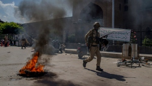 An Indian policeman walks past a burning tire set up as road block by Kashmiri protesters in Srinagar, Indian controlled Kashmir, Friday, May 25, 2018. Several people were injured after government forces fired pellet guns and tear gas shells on Kashmiris who gathered after Friday afternoon prayers protesting against Indian rule in the disputed region. (AP Photo/Dar Yasin)
