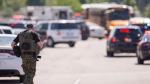 A law enforcement officer walks outside Noblesville West Middle School in Noblesville, Ind., after a shooting on Friday, May 25, 2018. A male student opened fire at the suburban Indianapolis school wounding another student and a teacher before being taken into custody, authorities said. (Robert Scheer/The Indianapolis Star via AP)