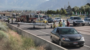 Emergency workers stand next to a plane which had to make an emergency landing on Interstate 15 in Riverdale, Utah on Saturday May, 26, 2018. (Matt Herp/Standard-Examiner via AP)
