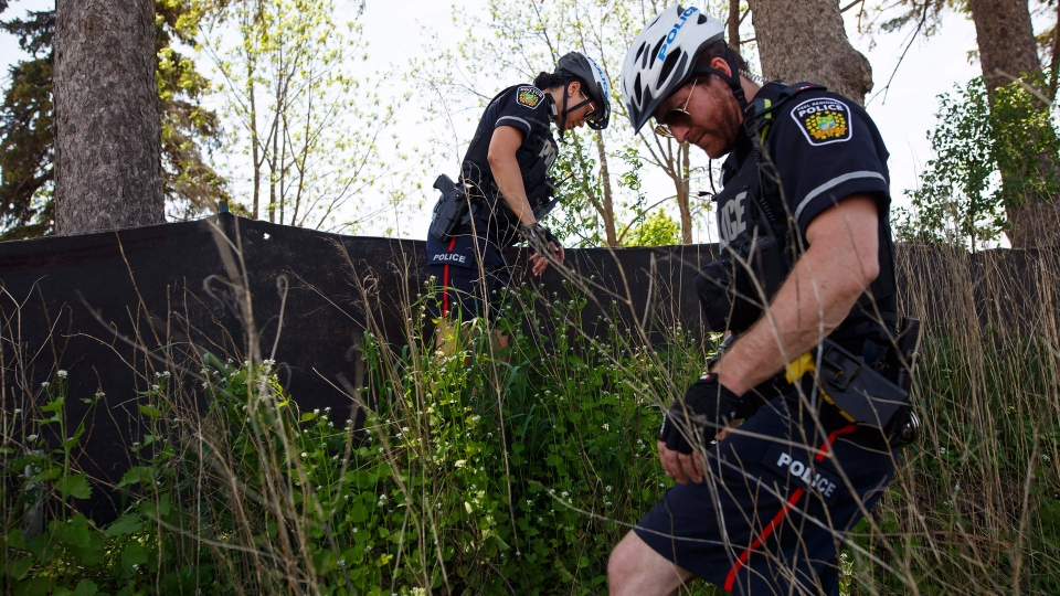 Police search around a wooded section near the scene of an explosion at a restaurant in Mississauga, Ont. on Friday, May 25, 2018. THE CANADIAN PRESS/Cole Burston