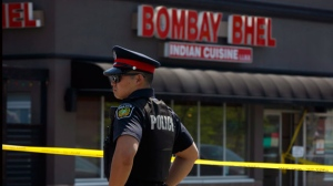 Police officers keep watch over the scene where an IED ripped through a Mississauga, Ont., restaurant early Friday morning, on Friday, May 25, 2018. (THE CANADIAN PRESS/Cole Burston)
