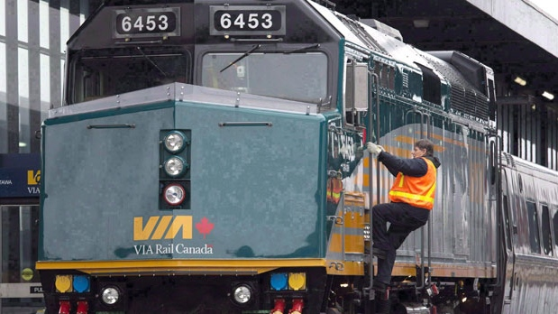 FILE - A Via Rail employee climbs aboard a locomotive at the train station in Ottawa on December 3, 2012. THE CANADIAN PRESS/Adrian Wyld