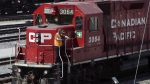 A Canadian Pacific Railway employee walks along the side of a locomotive in a marshalling yard in Calgary, Wednesday, May 16, 2012. THE CANADIAN PRESS/Jeff McIntosh