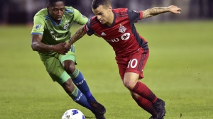 """Toronto FC forward Sebastian Giovinco moves past Seattle Sounders FC defender Kelvin Leerdam during second half MLS soccer action in Toronto on Wednesday, May 9, 2018. After a 3-7-1 start to the season, Toronto FC is desperate to turn things around. """"We have to change everything and try to make the playoffs,"""" said striker Sebastian Giovinco. THE CANADIAN PRESS/Frank Gunn"""