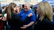 Ontario PC leader Doug Ford embraces York-Simcoe candidate Caroline Mulroney as Newmarket-Aurora candidate Christine Elliott looks on, at a breakfast meet and greet in Ottawa on Saturday, June 2, 2018. THE CANADIAN PRESS/Justin Tang