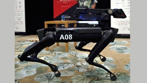 In this Thursday, May 24, 2018, photo a Boston Dynamics SpotMini robot is walks through a conference room during a robotics summit in Boston. It's never been clear whether robotics company Boston Dynamics is making killing machines, household helpers, or something else entirely. But the secretive firm, which for nine years has unnerved viewers with YouTube videos of robots that jump, gallop or prowl like animal predators, is starting to emerge from a quarter-century of stealth. (AP Photo/Charles Krupa)
