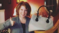 In this 2013 photo provided by Dennis Hauser, his wife Melanie Hauser, who writes as Melanie Benjamin, shows off her first bag designed by Kate Spade, posing for a photo at their home in Glen Ellen, Ill. After Spade's death by apparent suicide on Tuesday, June 5, 2018, fans mourned the designer and thanked her for fashion that marked formative moments in their lives. Melanie, who has since moved to Chicago, said she has other Kate Spade purses that are more colorful and fun. (Dennis Hauser via AP)