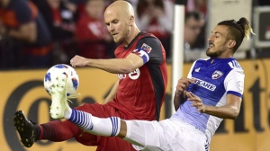 Toronto FC midfielder Michael Bradley (4) and FC Dallas forward Maximiliano Urruti battle for the ball during second half MLS soccer action in Toronto on Friday, May 25,18. Captain Michael Bradley has given his all to injury-ravaged Toronto FC as an emergency defender this season. But coach Greg Vanney knows that the team needs Bradley back in his role as holding midfielder. THE CANADIAN PRESS/Frank Gunn