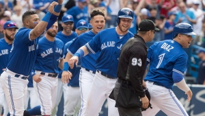 Toronto Blue Jays players pour on to the field to celebrate with Justin Smoak, third from right, who scored the winning run against the Baltimore Orioles on a bases loaded walk by teammate Luke Maile in the tenth inning of their American League MLB baseball game in Toronto on Saturday June 9, 2018. THE CANADIAN PRESS/Fred Thornhill