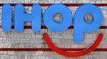 "This May 11, 2017, file photo shows an IHOP sign at a restaurant in Hialeah, Fla. IHOP, which teased a name change to IHOb earlier this month, says the ""b"" is to promote its burger menu. The pancake restaurant has been coy about whether the name change is truly permanent, saying Monday, June 11, 2018, that the change was ""for the time being."" (AP Photo/Alan Diaz, File)"