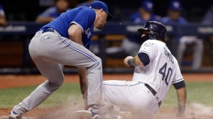 Tampa Bay Rays' Wilson Ramos (40) scores under the tag by Toronto Blue Jays relief pitcher John Axford (77) on a fielder's choice by Joey Wendle during the seventh inning of a baseball game Monday, June 11, 2018, in St. Petersburg, Fla. (AP Photo/Chris O'Meara)