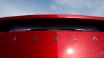 In this April 15, 2018, file photo the sun shines off the rear deck of a roadster on a Tesla dealer's lot in the south Denver suburb of Littleton, Colo. Electric car maker Tesla Inc. is laying off about 3,600 white-collar workers as it slashes costs in an effort to become profitable. CEO Elon Musk says in an e-mail to workers Tuesday, June 12, that the cuts amount to about 9 percent of the company's workforce of 40,000. (AP Photo/David Zalubowski, File)