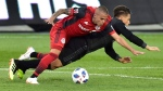 Toronto FC defender Auro (96) takes down D.C. United midfielder Yamil Asad (22) and picks up a yellow card on th eplay during first half MLS soccer action in Toronto on Wednesday, June 13, 2018. THE CANADIAN PRESS/Frank Gunn