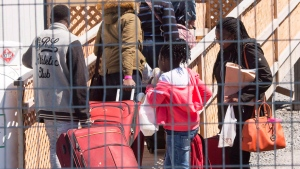 A group of asylum seekers arrive at the temporary housing facilities at the border crossing Wednesday May 9, 2018 in St. Bernard-de-Lacolle, Quebec. (Ryan Remiorz / THE CANADIAN PRESS)