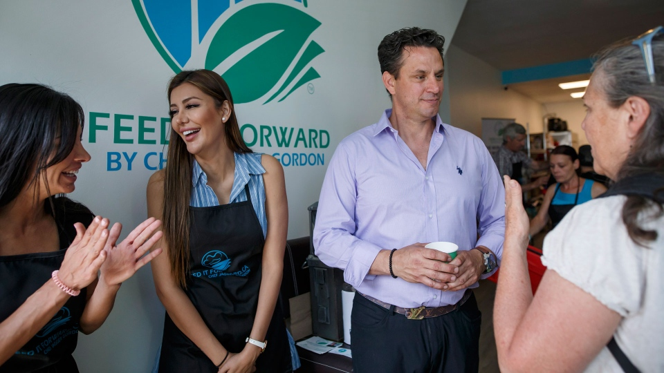 Chef Jagger Gordon, middle right, chats with customers at the Feed it Forward's Pay-what-you-can grocery store grand opening in Toronto, Ontario on Saturday, June 16, 2018. The new model grocery store, created by Chef Gordon is the first of it's kind in Toronto, encouraging those from different socioeconomic backgrounds to use and fuel the model to help curb food waste. THE CANADIAN PRESS/Cole Burston