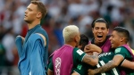 Germany goalkeeper Manuel Neuer walks past as Mexico players celebrate after defeating Germany 1-0 in their group F match at the 2018 soccer World Cup in the Luzhniki Stadium in Moscow, Russia, Sunday, June 17, 2018. (AP Photo/Eduardo Verdugo)
