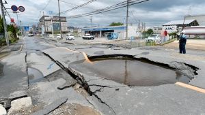 A crack is filled with water on a road after water pipes were broken following an earthquake in Takatsuki city, Osaka, western Japan, Monday, June 18, 2018. A strong earthquake knocked over walls and set off scattered fires around metropolitan Osaka on Monday morning. (Keiji Uesho/Kyodo News via AP)
