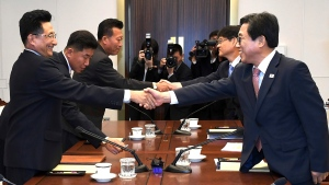 In this photo provided by the South Korea Culture And Sports Ministry, South Korean head delegate Jeon Choong-ryul, right, shakes hands with his North Korean counterpart Won Kil U during a meeting at the southern side of Panmunjom in the Demilitarized Zone, North Korea, Monday, June 18, 2018. Sports officials from the rival Koreas are meeting at a border village to discuss how to cooperate in the Asian Games being held in Indonesia in August. (South Korea Culture And Sports Ministry via AP)
