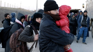 In this Sunday, Jan. 24, 2016, file photo, refugees and migrants wait to embark in police and military vans on a highway near the northeastern Greek village of Thourio, at the Greek-Turkish border. (AP Photo/Thanassis Stavrakis, file