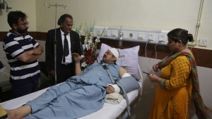 In this Wednesday, June 6, 2018 photo, Pakistani TV anchorman Asad Kharal talks to visitors after he was stabbed by masked men near his residence, at a hospital in Lahore, Pakistan. The Vienna-based Independent Press Institute, an international watchdog, said in a report released Monday, June, 18, 2018, that Pakistan's military is strong-arming the media in an attempt to stifle criticism of its behind-the-scenes political power ahead of next month's elections. The report documented a nationwide campaign of intimidation, including everything from threats to abductions. (AP Photo/K.M. Chaudary)