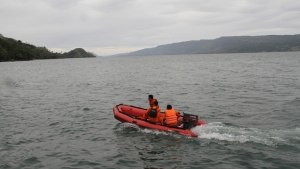 Indonesian search and rescue team on the boat search for a ferry carrying about 80 passengers which sank on Monday, in Toba lake, North Sumatera, Indonesia, Tuesday, June 19, 2018. A night-time search and rescue effort is underway after a ferry carrying about 80 passengers sank Monday in a popular lake on the Indonesian island of Sumatra.(AP Photo/ Lazuardy Fahmi)