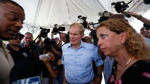 U.S. Sen. Bill Nelson, center and congresswoman Debbie Wasserman Schultz, right, were denied entry by security into the Homestead Temporary Shelter for Unaccompanied Children on Tuesday, June 19, 2018, in Homestead, Fla. (AP Photo/Brynn Anderson)