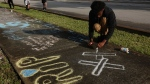 Lenar Nesmith, of Pompano Beach, Fla., a fan of rap singer XXXTentacion, writes a message on the sidewalk, Tuesday, June 19, 2018, outside Riva Motorsports in Deerfield Beach, Fla., where the troubled rapper-singer was killed the day before. The 20-year-old rising star, whose real name is Jahseh Dwayne Onfroy, was shot outside the motorcycle dealership on Monday, June 18, when two armed suspects approached him, authorities said. (Joe Cavaretta/South Florida Sun-Sentinel via AP)
