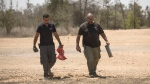 "Israeli police sapper and a security guard remove a missile launched from Gaza Strip inside a kibbutz in Israel near the border with Gaza, Wednesday, June 20, 2018. Israel's military says its warplanes have struck some 25 Hamas positions in Gaza after Palestinian militants fired dozens of rockets and mortars at southern communities. The fire came hours after the military said it struck Hamas infrastructure in response to ""arson balloons"" launched from Gaza to Israel. (AP Photo/Tsafrir Abayov)"