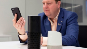 In this June 14, 2018, photo, Gareth Gaston, Executive Vice President and Head of Omnichannel Banking at US Bank, discusses voice assistant banking with a mobile phone, an Amazon Echo, center, and a Google Home, right, in New York. (AP Photo/Mark Lennihan)