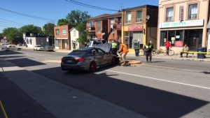 Police are shown at the scene of a collision involving a car and a TPS motorcycle near Eglinton Avenue West and Oakwood Avenue. (Courtney Heels)
