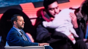 Italian Interior Minister Matteo Salvini, backdropped with a photograph of migrants being rescued at sea, attends a talk show on RAI state television, in Rome, Wednesday, June 20 2018. (Angelo Carconi/ANSA via AP)