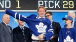 Rasmus Sandin, of Sweden,puts on a jersey after being selected by the Toronto Maple Leafs during the NHL hockey draft in Dallas, Friday, June 22, 2018. (AP Photo/Michael Ainsworth)