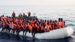 In this photo taken on Thursday, June 21, 2018, migrants on a rubber boat are being rescued by the ship operated by the German NGO Mission Lifeline in the Mediterranean Sea in front of the Libyan coast. (Hermine Poschmann/Mission Lifeline via AP)