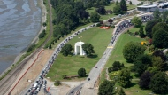 In this July 24, 2009 file photo, cars line-up heading into the United States at left and into Canada at right adjacent to Boundary Bay at a border crossing at Blaine, Wash.  A 19-year-old woman who traveled from France to Canada to visit her mother in British Columbia says U.S. officials detained her for two weeks after she accidentally crossed the border while jogging. Cedella Roman tells the Canadian Broadcast Co. that two U.S. Customs and Border Protection agents apprehended her on May 21, 2018 on a beach south of White Rock, British Columbia. Roman says she didn't have identification and was transferred to the Tacoma Northwest Detention Center run by the Department of Homeland Security.  (AP Photo/Elaine Thompson)