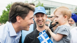 Prime Minister Justin Trudeau, left, greets a man and young girl during a visit to a Saint-Jean Baptiste day celebration in Montreal, Saturday, June 23, 2018. THE CANADIAN PRESS/Graham Hughes