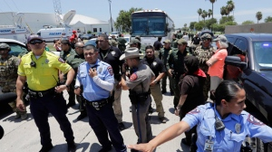 Law enforcement officials secure the street to allow a bus with immigrant children aboard to move out after protestors blocked it outside the U.S. Border Patrol Central Processing Center Saturday, June 23, 2018, in McAllen, Texas.   The protest occurred amid an uproar over the Trump administration's practice of separating immigrant families caught on the southwest border. President Donald Trump signed an order this week to keep families detained together during immigration proceedings. (AP Photo/David J. Phillip)