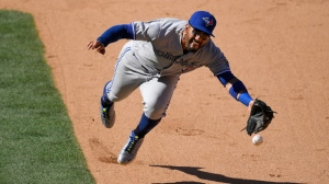 Toronto Blue Jays second baseman Devon Travis flips the ball to first in an attempt to throw out Los Angeles Angels' Justin Upton at first during the 10th inning of a baseball game Sunday, June 24, 2018, in Anaheim, Calif. Upton was safe at first on the play. (AP Photo/Mark J. Terrill)
