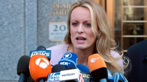 In this April 16, 2018, file photo, adult film actress Stormy Daniels speaks outside federal court in New York. A federal judge on Tuesday, June 19, denied porn actress Stormy Daniels' request to reconsider delaying her legal fight against President Donald Trump and his personal lawyer. (AP Photo/Mary Altaffer, file)