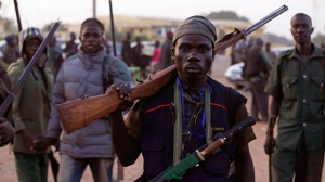 In this file photo taken on Wednesday, Nov. 25, 2014 file photo, vigilantes and local hunters armed with locally made guns gather before they go on patrol in Yola, Nigeria.  (AP Photo/Sunday Alamba, File)