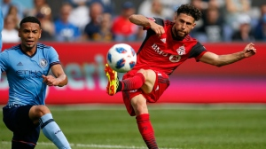 Toronto FC midfielder Jonathan Osorio, right, shoots on goal in front of New York City FC defender Alexander Callens during the first half of an MLS soccer game Sunday, June 24, 2018, in New York. (AP Photo/Adam Hunger)