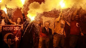 In this photo taken late Sunday, June 24, 2018, supporters of Turkey's President and ruling Justice and Development Party, or AKP, leader Recep Tayyip Erdogan light flares during celebrations outside the party headquarters in Istanbul. According to unofficial results, Erdogan won 52.6 percent of the votes in the presidential race, avoiding a second-round runoff vote. His ruling Justice and Development Party garnered 42.5 percent of the parliamentary vote. (AP Photo/Emrah Gurel)
