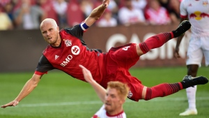 Toronto FC midfielder Michael Bradley (4) falls to the ground after getting off a shot on goal during second half MLS soccer action against the New York Red Bulls, in Toronto on Sunday, July 1, 2018. THE CANADIAN PRESS/Frank Gunn