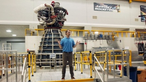 Tom Martin, launch strategy and business development director for Aerojet Rocketdyne, talks to media in front of one of the AR-22 engines for a developmental reusable spacecraft in Stennis, Miss., Monday, July 2, 2018. Triggering a massive cloud of vapor and a roar, officials on Monday test fired a rocket engine designed to be part of a reusable spacecraft that can launch into space repeatedly with a quick turnaround time. (AP Photo/Gerald Herbert)