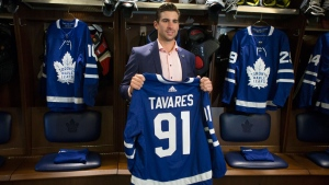 John Tavares holds up a jersey bearing his name in the Maple Leafs' locker room following a news conference in Toronto after signing with the Toronto Maple Leafs on Sunday July 1, 2018.THE CANADIAN PRESS/Chris Young