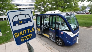 In this June 4, 2018, photo, an Mcity driverless shuttle makes a stop on the University of Michigan in Ann Arbor, Mich. Dozens of self-driving shuttles made by French autonomous vehicle company Navya are now ferrying passengers at hospitals, airports and public roads worldwide. Last week the University of Michigan began running two of its shuttles on a part of its campus. (AP Photo/Paul Sancya)