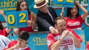 George Shea, top center, announces and points towards reigning champion Joey Chestnut, bottom right, during the men's competition of the Nathan's Famous Fourth of July hot dog eating contest in the final seconds of the competition, Wednesday, July 4, 2018, in New York's Coney Island. Chestnut broke his own world record by eating 74 hot dogs in 10 minutes. (AP Photo/Mary Altaffer)